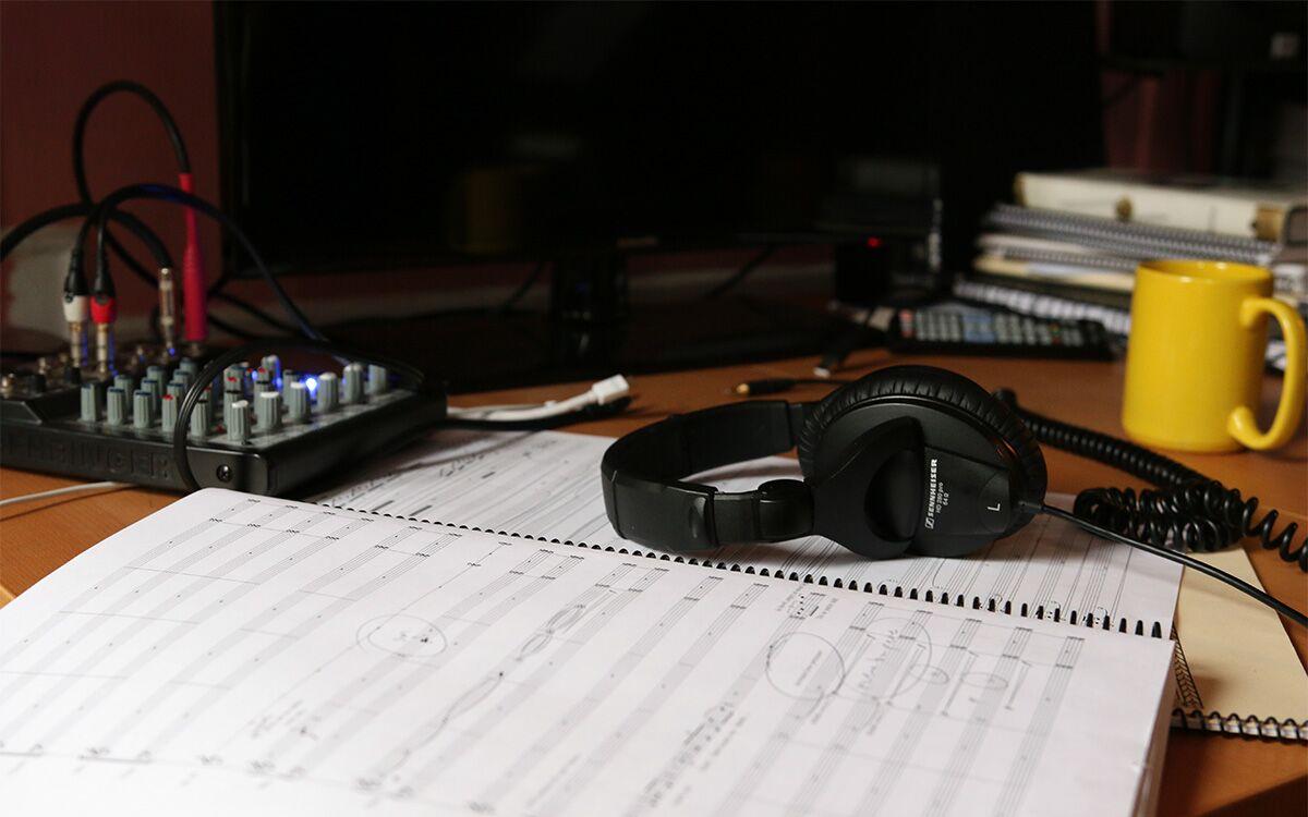 A printed score manuscript, headphones, and a coffee mug.