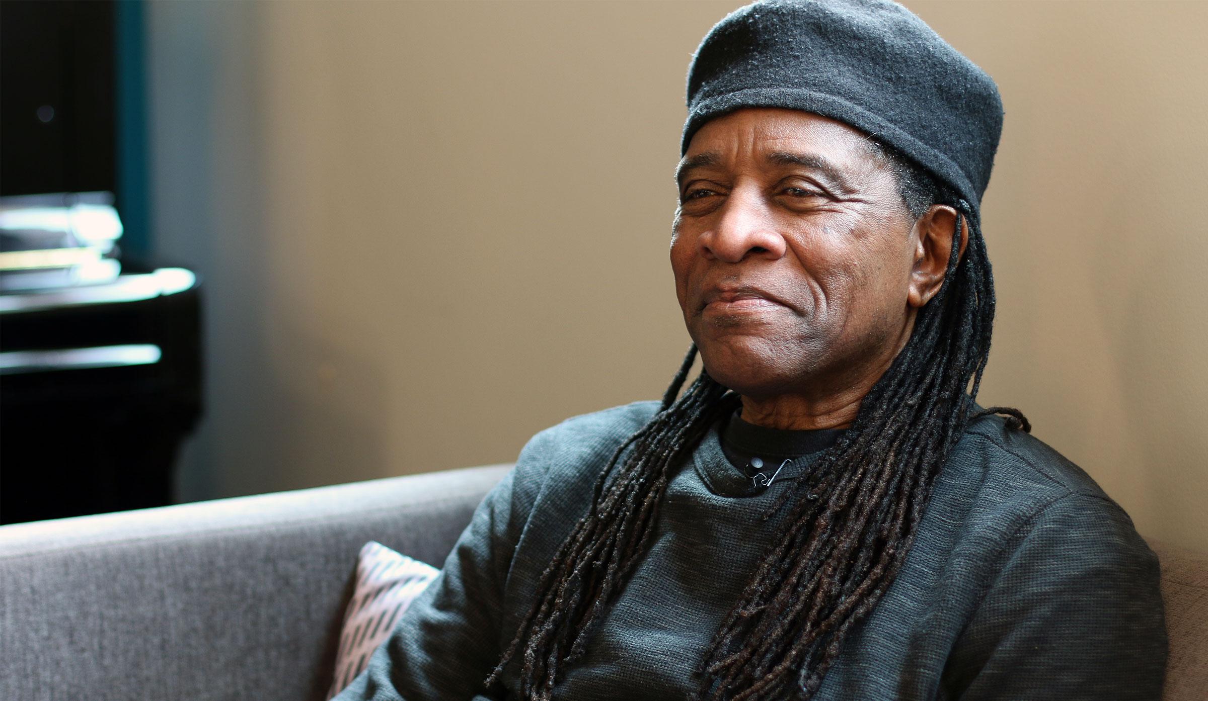 A BIPOC man with dreads, a dark shirt, and dark cap
