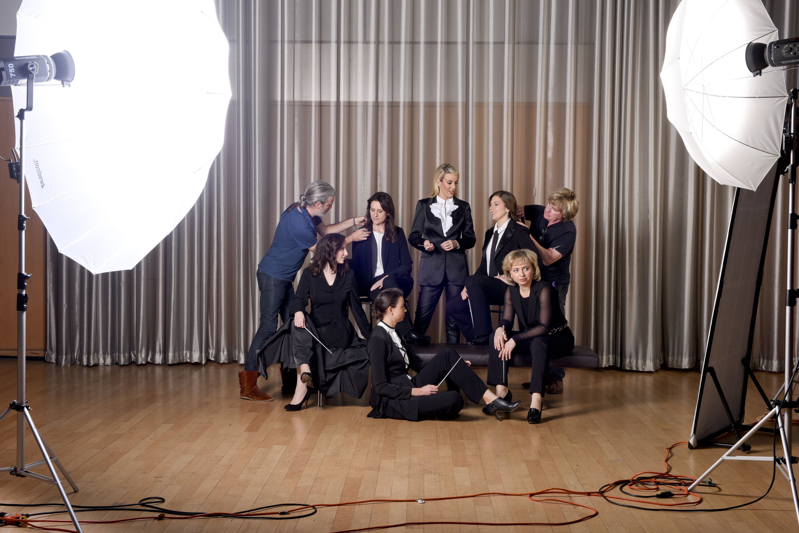 Six of the female conductors participating in the Hart Institute posing in tuxedos with batons for a photo shoot as two others help them adjust their positions for the camera.