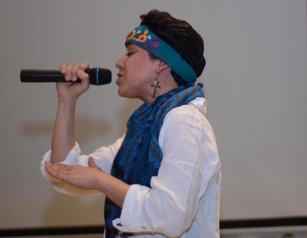 Nejma Nefertiti holding a microphone.