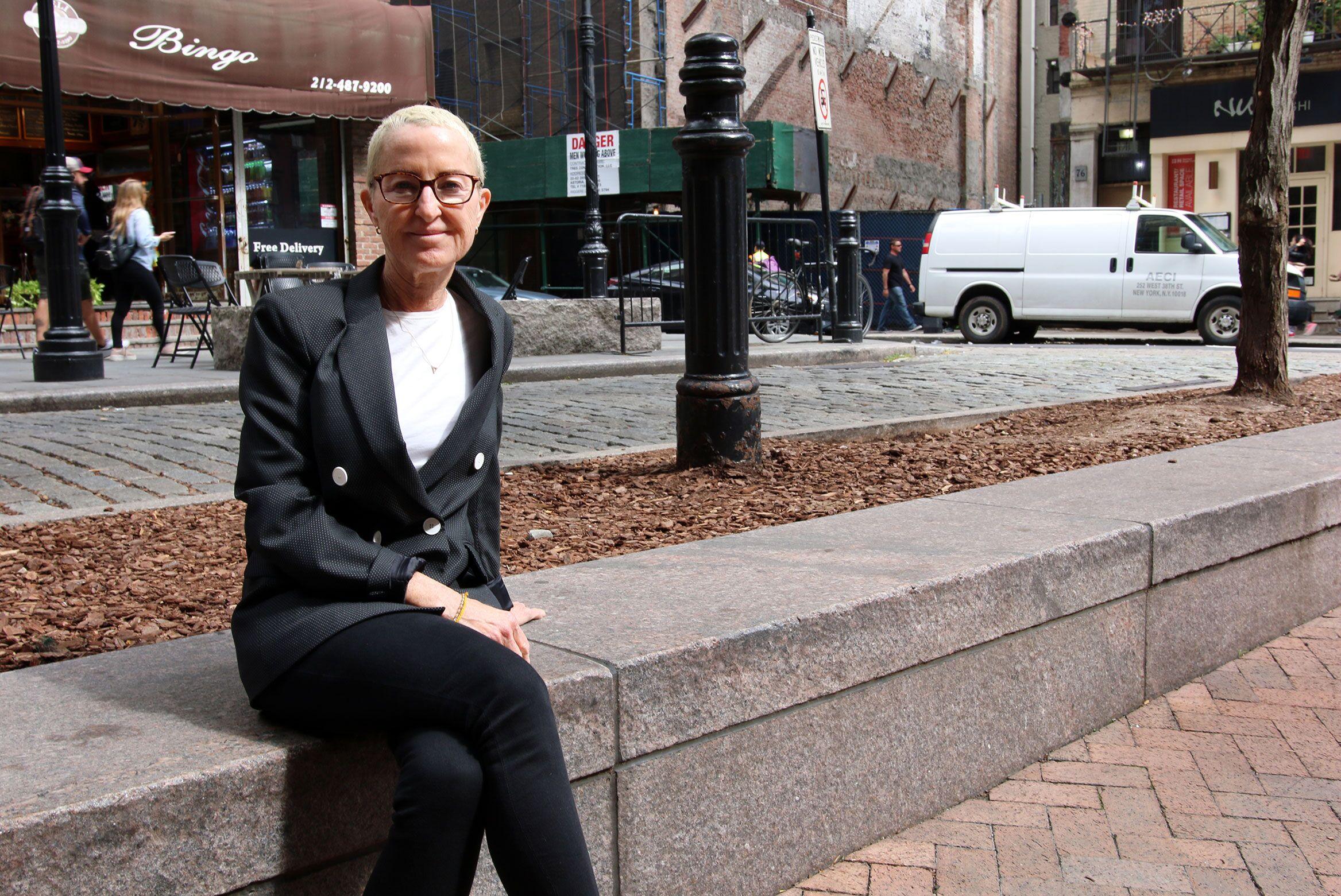 Myra Melford sitting outside near a sidewalk in New York City.