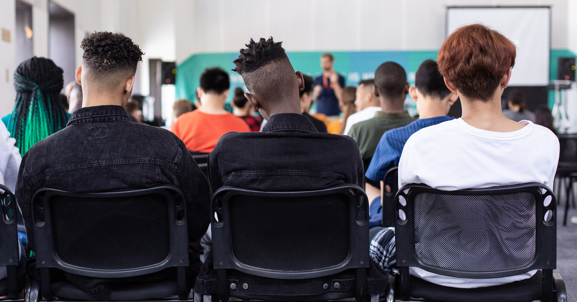 Photo by Sam Balye viaUnsplash of a crowded classroom from the back of the room showing a diverse group of students