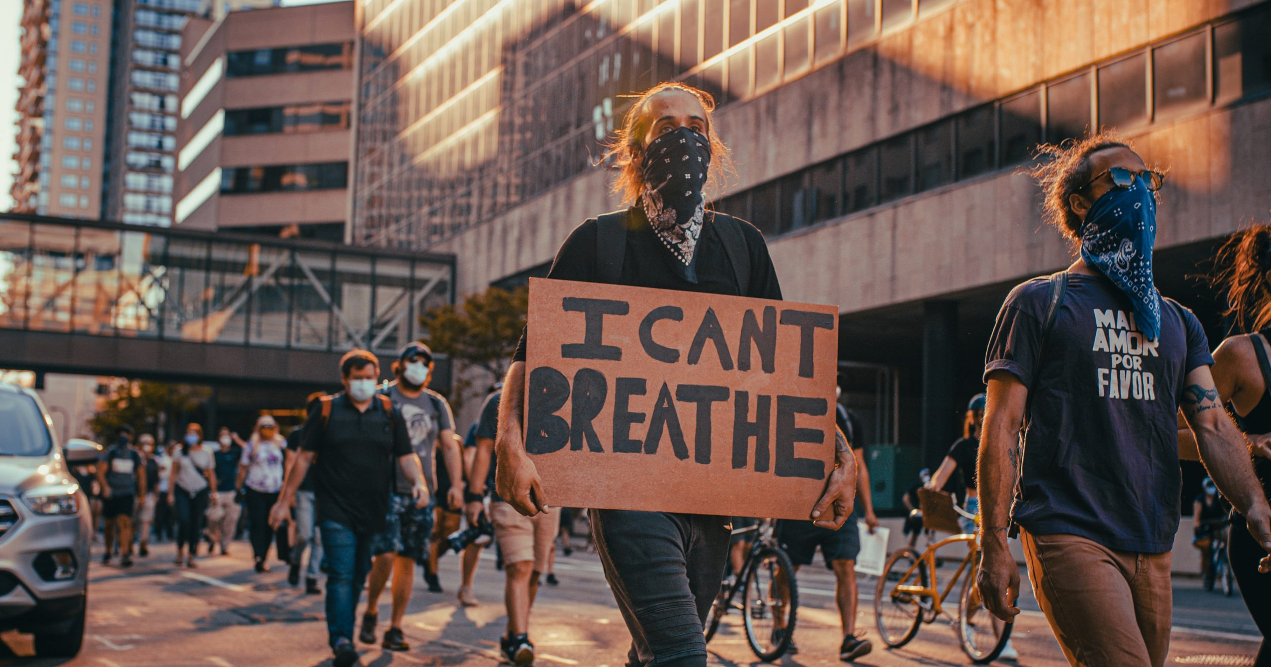 """A protester carrying a banner stating """"I CAN'T BREATHE."""" Photo by Josh Hild on Unsplash"""