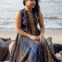 Anjna Swaminathan sitting on a rock at a beach by the water.