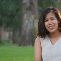 An outdoor photo of an AAPI woman in a white, cream top