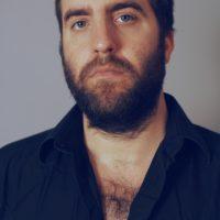 A Caucasian man in a black, button-up shirt and beard