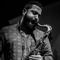 A black & white image of Hery playing a tenor saxophone.