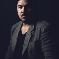 A dark shot of a Filipino-Arab-American man with a charcoal grey blazer