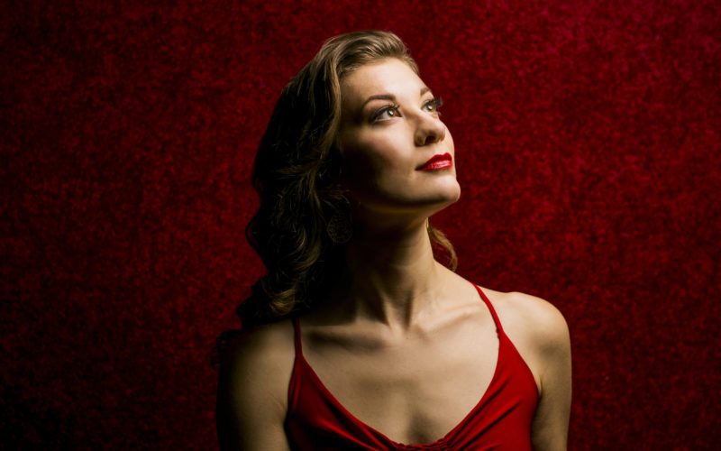 A woman in red against a red background, looking into the distance