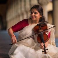 A cross-legged woman in a sari holding her violin