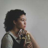 A woman posing with a baritone saxophone in a black-and-white striped shirt, head tilted