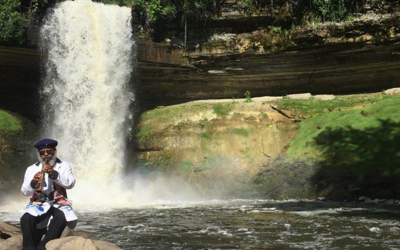 Douglas R. Ewart plays an instrument by a waterfall