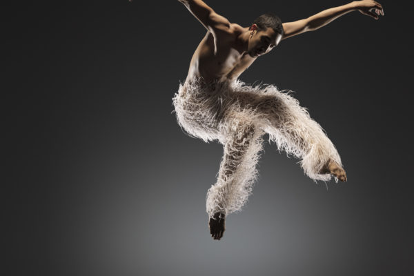 A dancer wearing feathered pants jumps