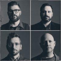 A foursquare black-and-white photo of four men