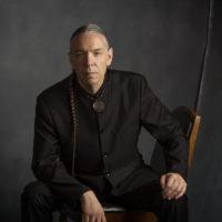 A Chickasaw man sitting with a dark background