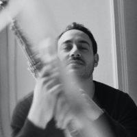 Yacine holding a blurred saxophone