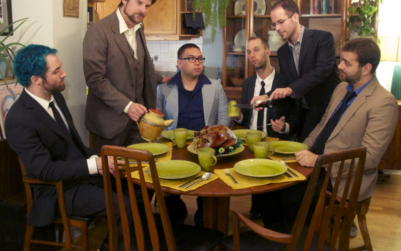 Six musicians stand around a roasted turkey in a quaint dining room