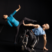 Two dancers, one in a wheelchair, posing horizontally and opposite one another.