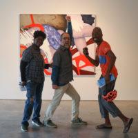 Three people posing in an art exhibit.