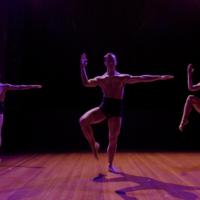 Three dancers pose identically in a dimly lit studio