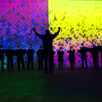 A conducted vocal group singing in the dark against colorful graphics.